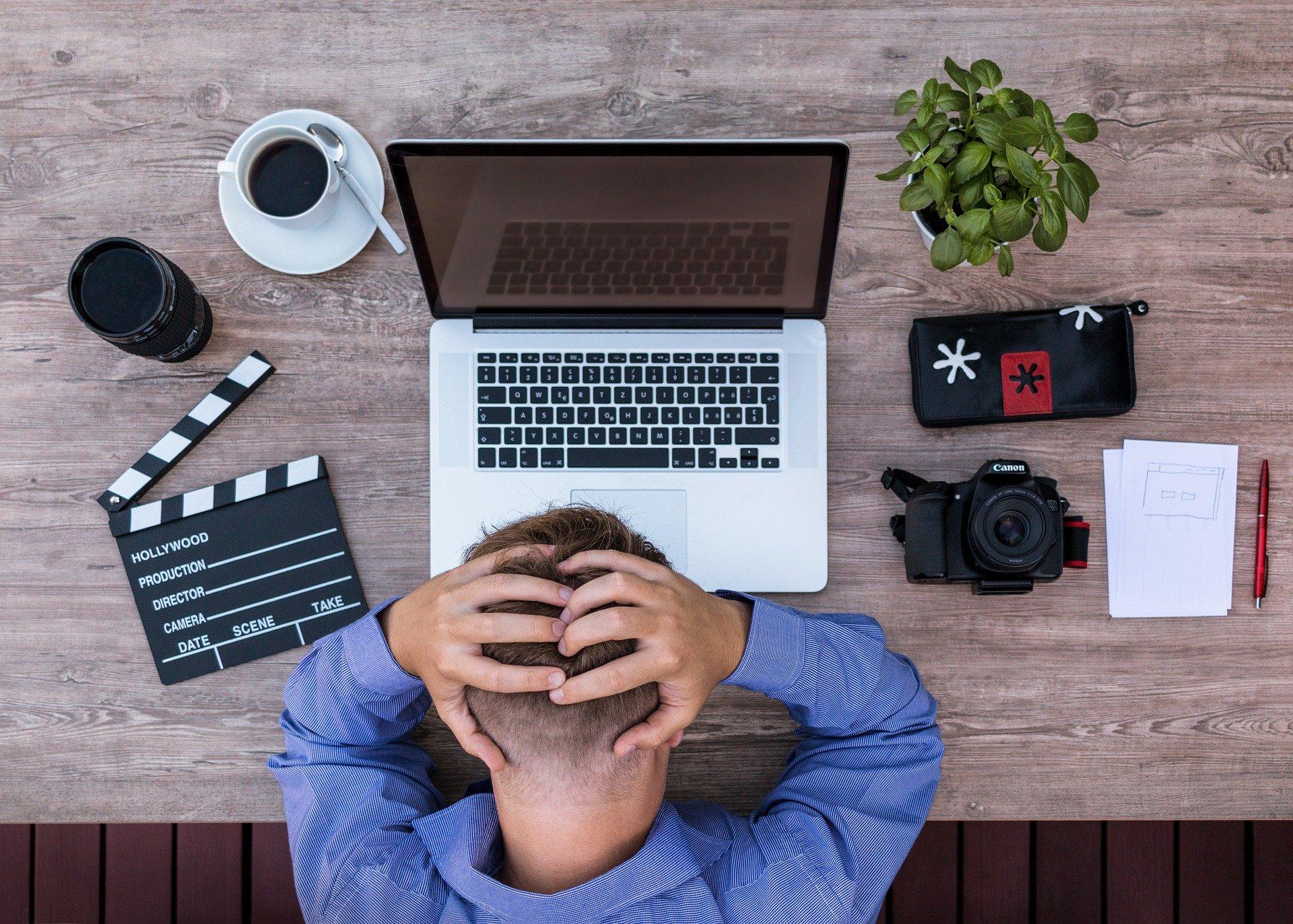 Een foto van een man achter zijn laptop, van bovenaf gezien. De man grijpt met zijn handen naar zijn hoofd. Op het bureau staat een plantje en er ligt o.a. een camera, een etui en een filmklapper.